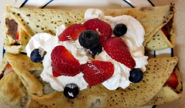 Crepes on a plate topped with whipped cream blueberries and sliced strawberries