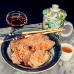 A bowl of potstickers with teapot, tea cup, dipping sauce, and chopsticks