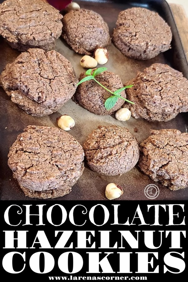 A baking sheet of Chocolate Hazelnut Cookies with a sprig of min and some hazelnuts