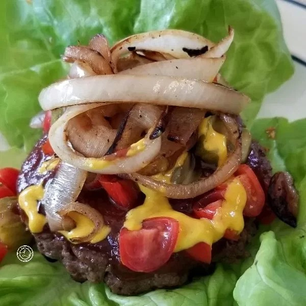 Cooked burger with toppings on butterhead lettuce