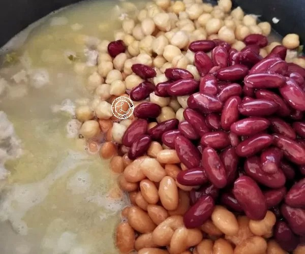 adding beans with water to the cooked vegetables and ground turkey