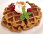 Two waffles on a plate with whipped cream, cranberries, and a sprig of mint.
