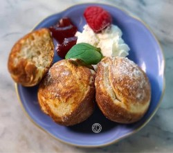 A tiny blue plate with three Danish Pancakes, jam, whipped cream, a raspberry, and sprig of mint