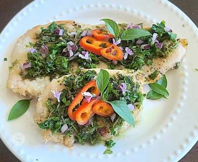 Marinated Chimichurri Chicken on a plate. Decorated with basil, basil flowers, and red bell peppers.