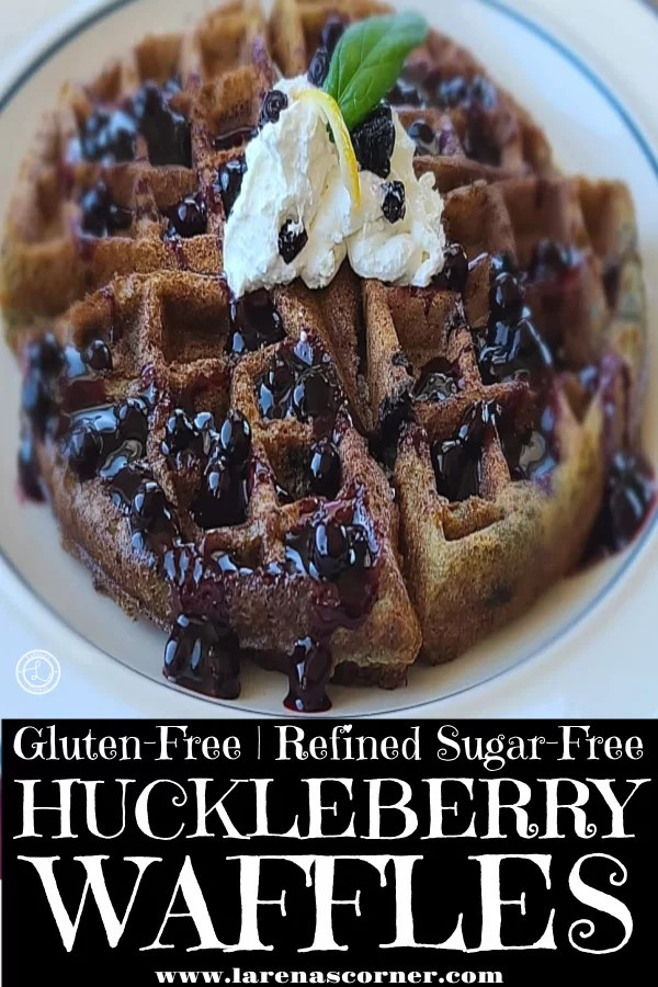 Gluten-Free Huckleberry Waffles up close picture with Huckleberry sauce on top, whipped cream, mint leaf, and lemon peel.
