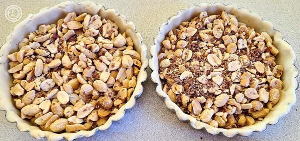 Adding chopped peanuts to tart shells