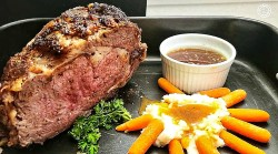 Roast in a roasting pan with mashed potatoes, carrots, gravy, and au jus.