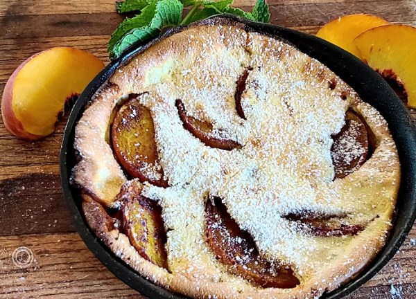 The top of Gluten-Free German Peach Pancakes two 6 inch individual pancakes with peaches looking out