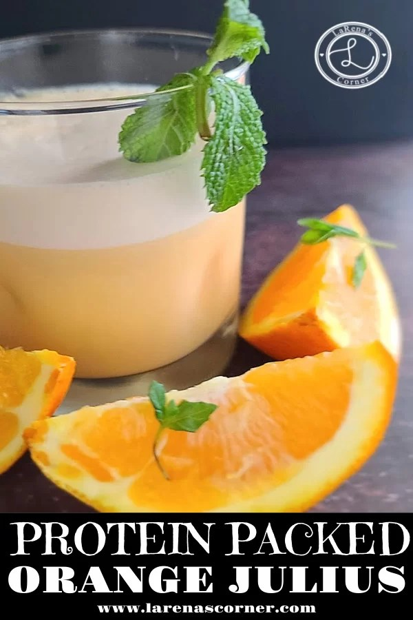 A picture of a glass of Orange Julius with orange slices and a sprig of mint