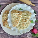 A picture of Gluten-Free Almond Poppyseed Scones on a cake platter with a platter of scones below.
