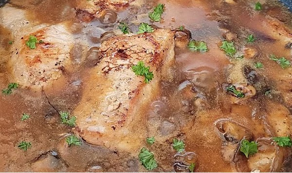 Adding Tapioca Flour to Smothered Onion-Mushroom Pork Chops in a pan with the gravy.