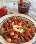 A gluten-free fresh strawberry waffle on a white plate.