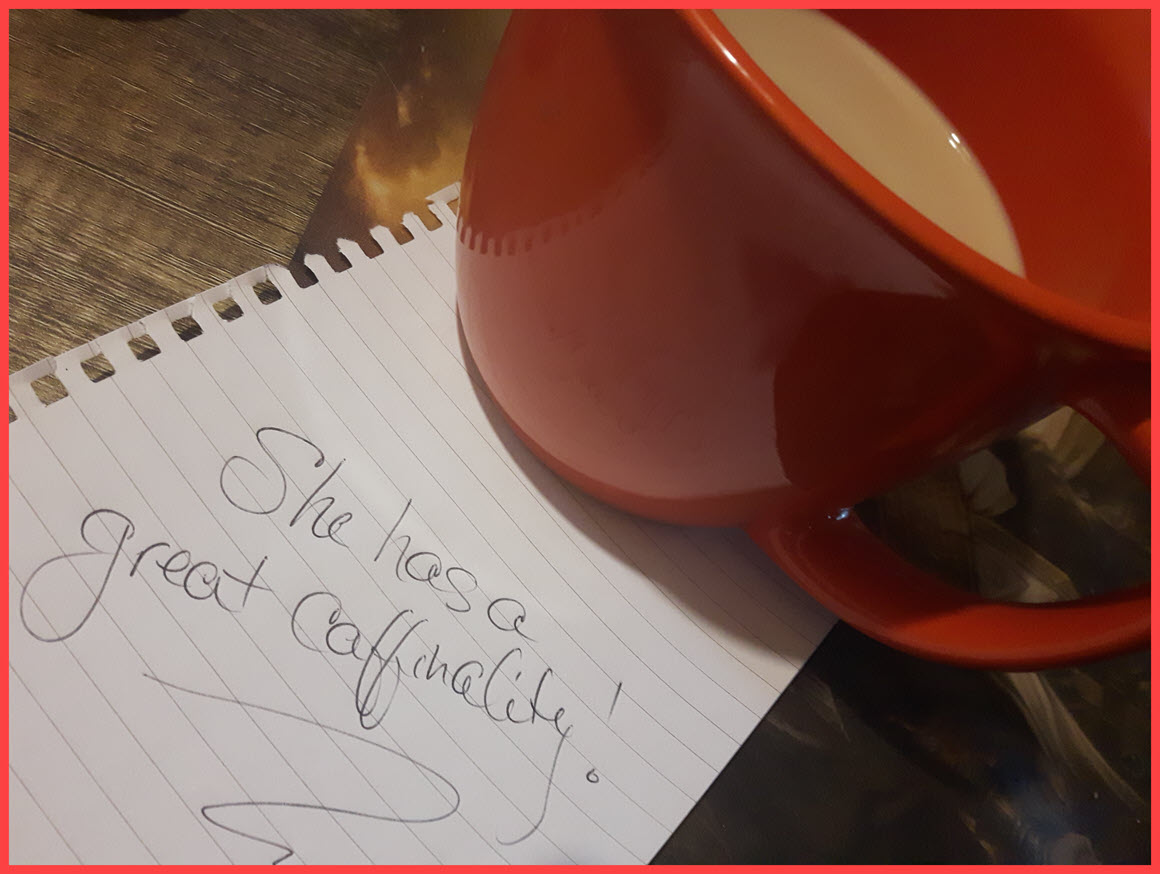 """red coffee cup on a note that has """"she has a great caffinality"""" written on it."""