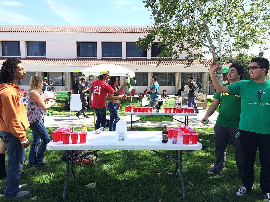 Saddleback College students gather to play root beer pong in the quad during the March Club Rush yesterday on March 17, 2014.