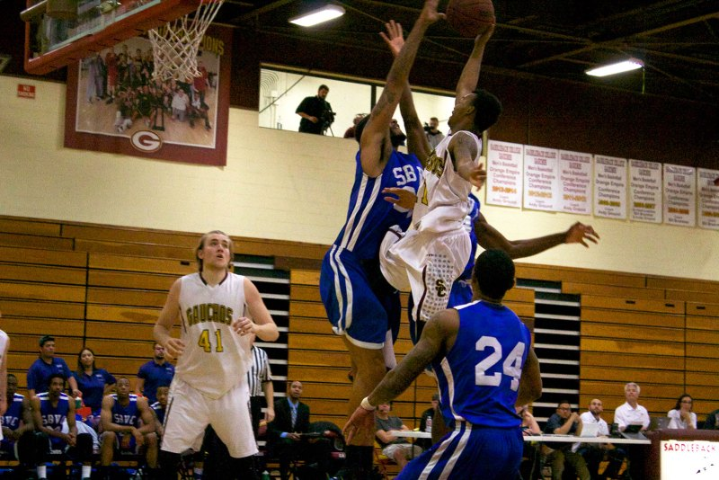 Sophomore forward Collin Host gets fouled as he attempts a lay-up over a Wolverine player. (Photo by Niko LaBarbera)
