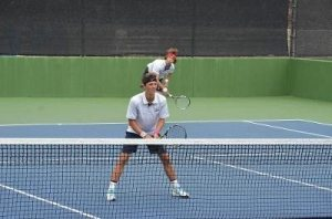 IVC sophomore Simon Guillin (front, left) and Guillermo Ucelay (back, right) playing in the first doubles match of the day.