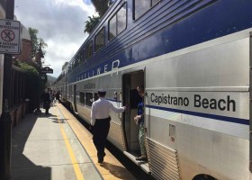 An Amtrak worker watches riders board the Surfliner train in San Juan Capistrano. (Kurtis Rattay/ Lariat)