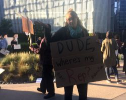 Activist holding a sign outside of Rep. Walters' office representing the 45th district. (Lesley Naranjo/ Lariat)