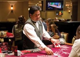 A casino blackjack dealer deals a card. (Wiki Commons)