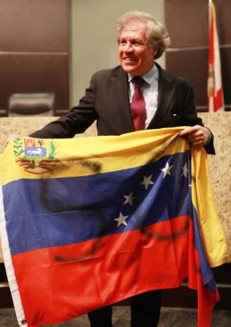 Luis Almagro toma una bandera venezolana a la que han manchado con pintura escribiendo SOS. El gesto es considerado como ofensivo, toda vez que implica un atentado contra un símbolo patrio