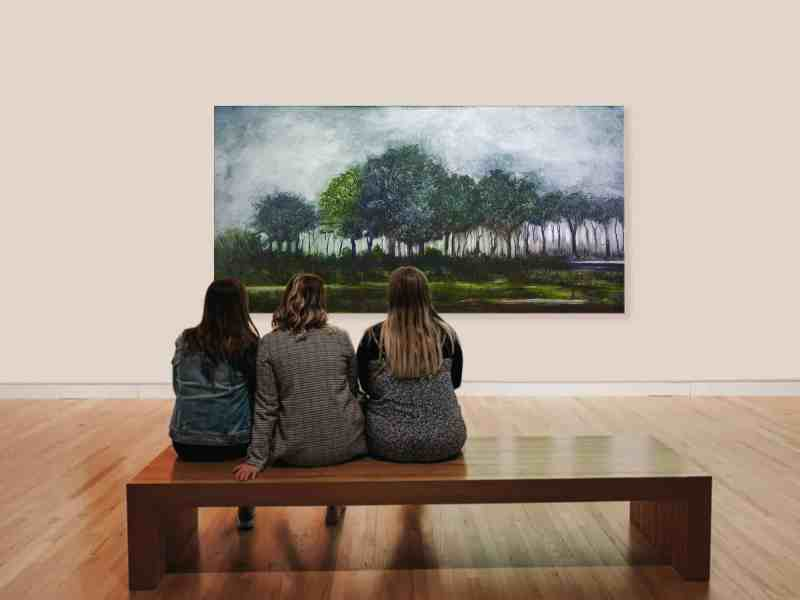 three women on a bench viewing a landscape painting by Mark Laurence LaRiviere