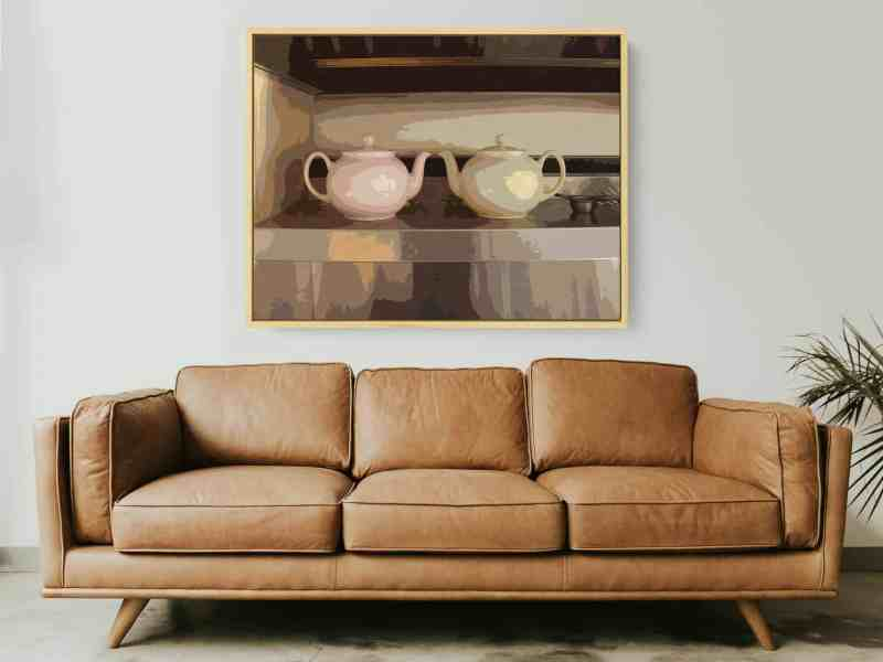 twin teapots wall art above leather sofa