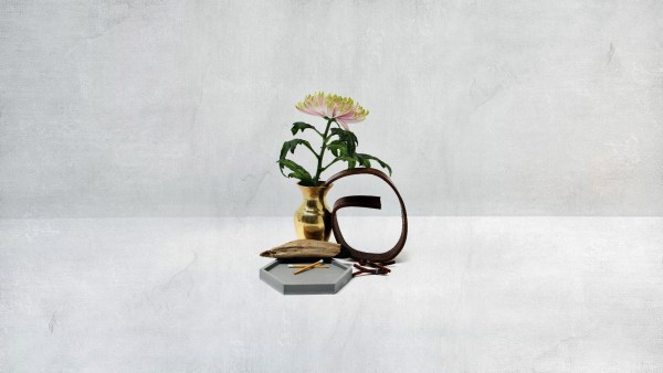 stunning chrysanthemum in a brass vase with leather coiled around it
