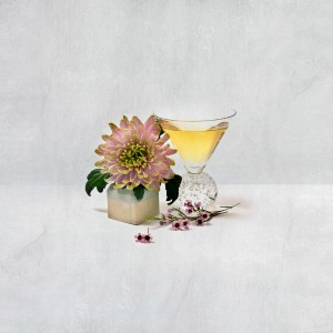 Chrysanthemum and other fresh flowers beside a chilled glass of champagne