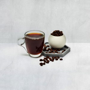 fresh cuppa coffee with coffee beans scattered around