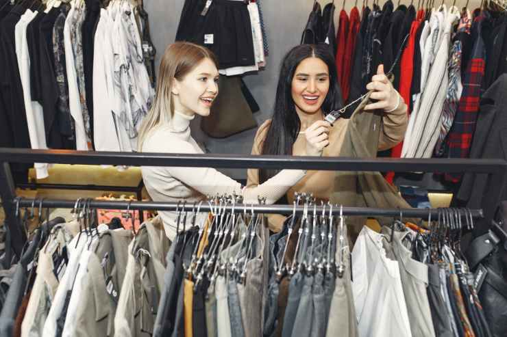 happy friends choosing clothes in store