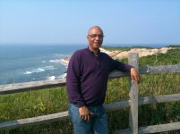 photo of Billy Childs standing beside a wooden fence at Martha's Vineyard, beach and ocean in the background