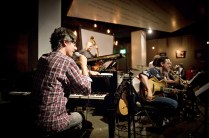 photo of Josh Nelson at grand piano speaking into microphone, Larry Koonse seated with guitar