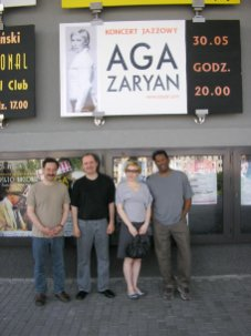photo of Larry Koonse with Aga Aaryan, Darek Oles, and Munyungo Jackson beneath sign advertising Aga Zaryan show