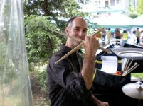 photo of Musician Mark Ferber holding drumsticks in outdoor setting