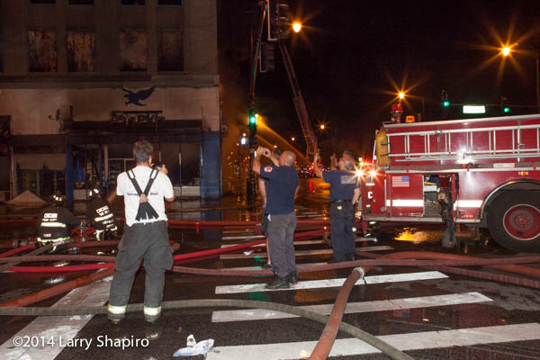 ire men with cellphones at fire scene