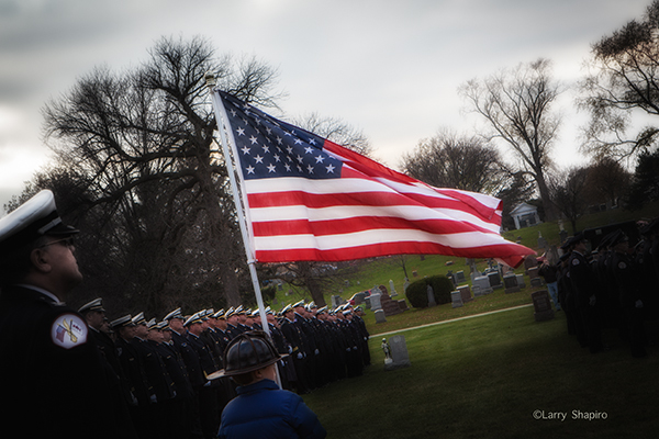 dramatic photo with the American flag at a funeral