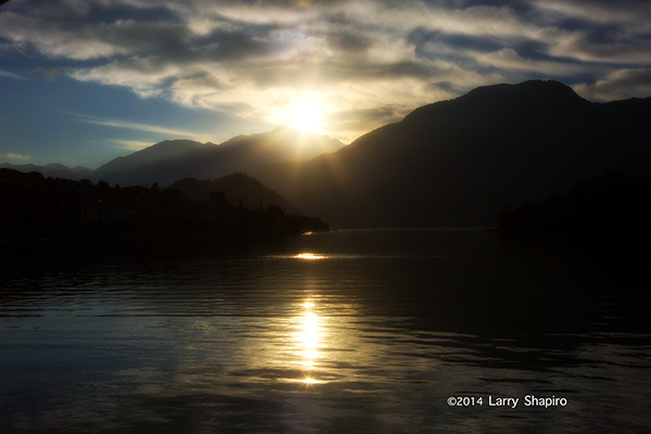 sun rising above mountains and reflecting into a lake