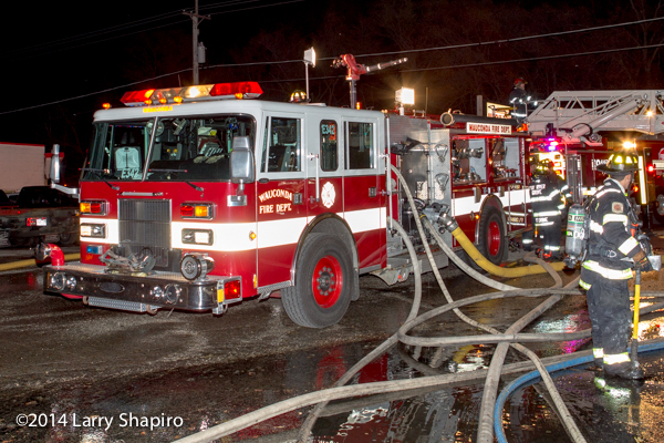 Pierce fire engine with lots of hose at night