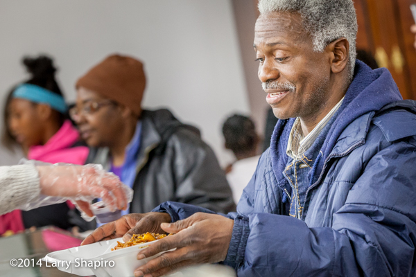 man receiving food at a soup kitchen