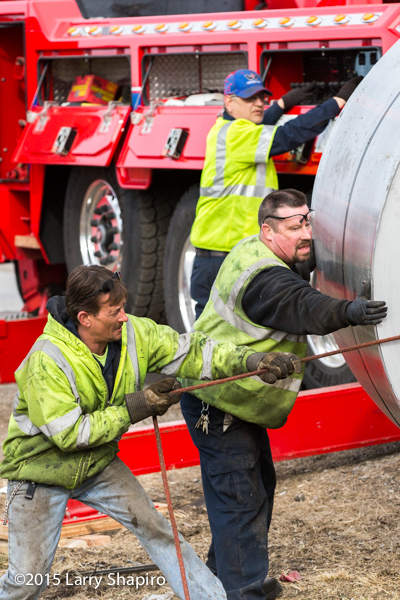 workers guide steel coils at a crash site