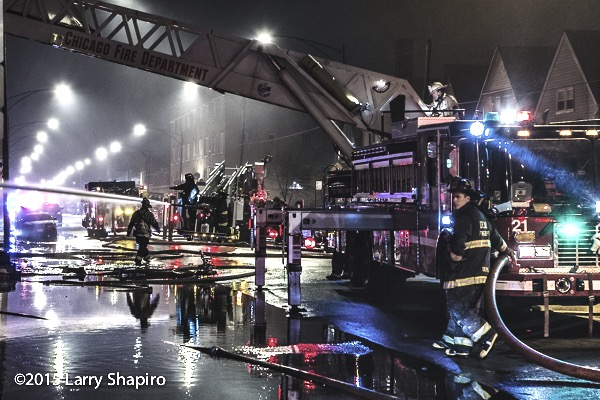 night fire scene in Chicago with trucks and water reflections