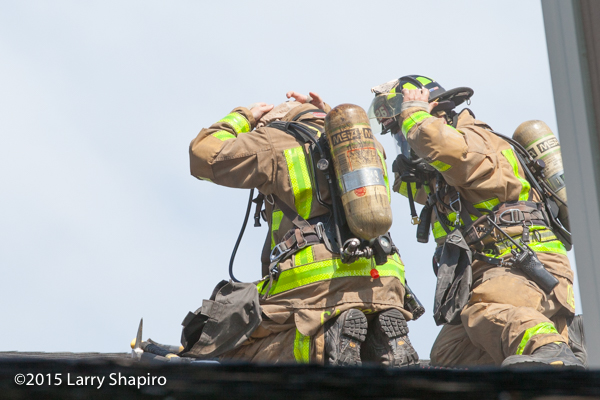firemen on the roof of a building