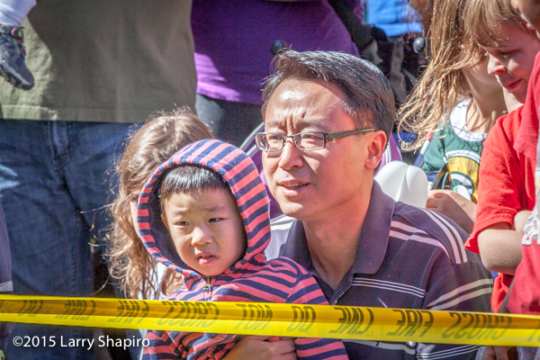 Asian father and son watching a demonstration of firefighters