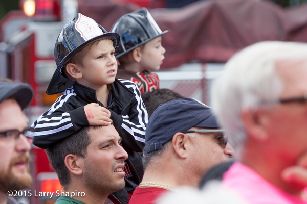 father with son on his shoulders in a crowd with a fire helmet