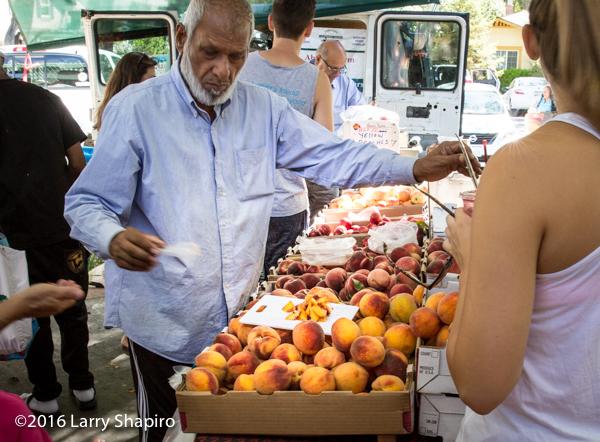 vendor with fresh peaches at framer's market