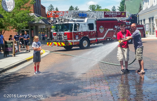 boys wet street with fire hose