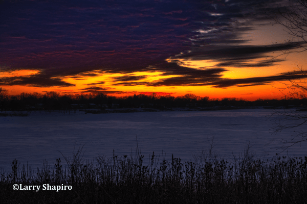 dramatic sunset over a snow covered lake