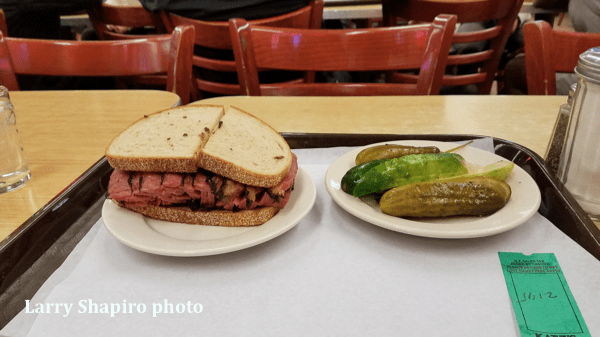 pastrami sandwich and pickles inside Katz's Deli in NYC