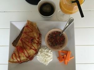 Omelet af æg med tomater, løg og skinketern Ovenpå omeletten er der stærk chili. Serveret med hytteost, gulerødder og havregryn med skyr, nødder, tørrede hindbær, chia-frø og proteinpulver med chokolade. Dertil kaffe og friskpresset appelsinjuice med ingefær.