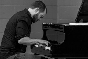 Lars at piano in black and white.